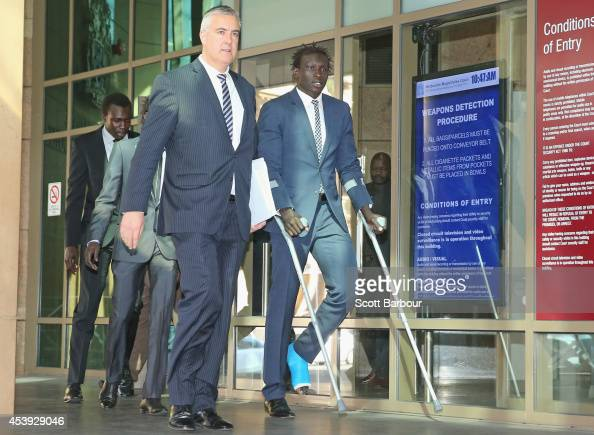 AFL player Majak Daw of the North Melbourne Kangaroos leaves on crutches after appearing in Melbourne Magistrates Court on August 22 2014 in...