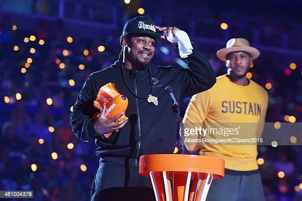 NFL player Marshawn Lynch accepts the Biggest Powerhouse award from NBA player Carmelo Anthony onstage at the Nickelodeon Kids' Choice Sports Awards...