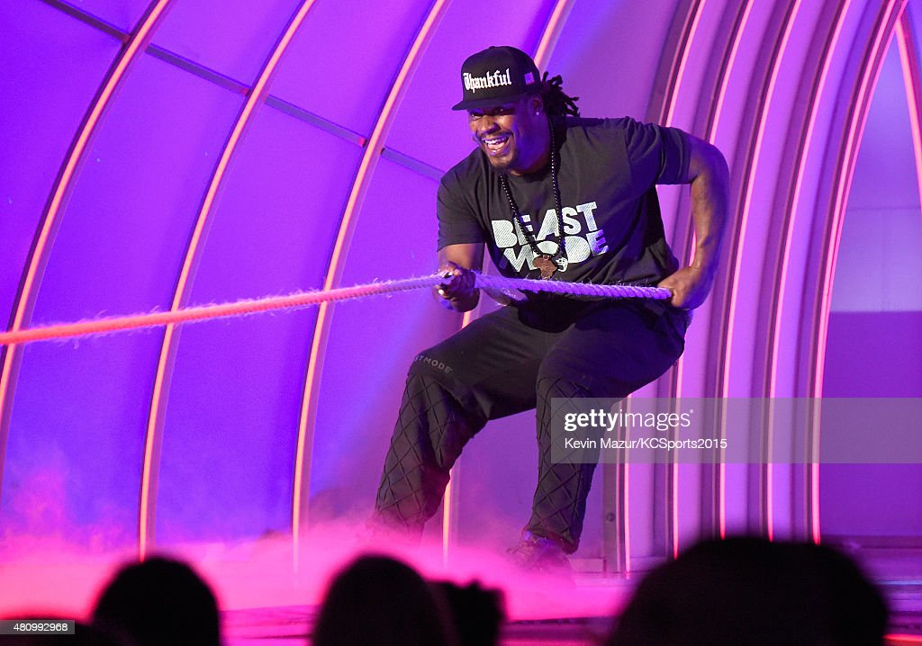 NFL player Marshawn Lynch plays tug-of-war onstage at the Nickelodeon Kids' Choice Sports Awards 2015 at UCLA's Pauley Pavilion on July 16, 2015 in Westwood, California.