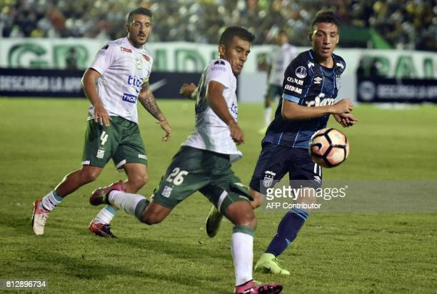 Player Nicolas Roman and Carlos Anez of Oriente Petrolero of Bolivia vie for the ball with Alejandro Melo of Atletico Tucuman of Argentina during...
