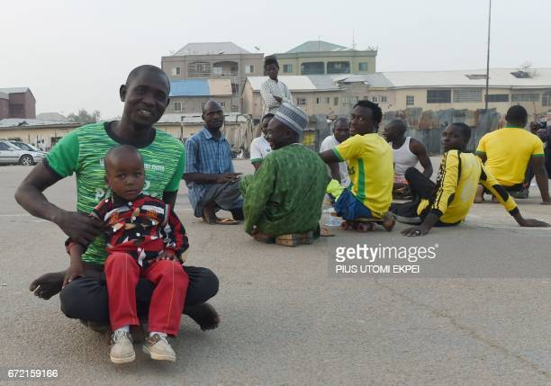 A player of Kano Pillars parasoccer team Suleiman Auta holds his son Khalid after a training session in Kano northwestern Nigeria on April 22 2017...