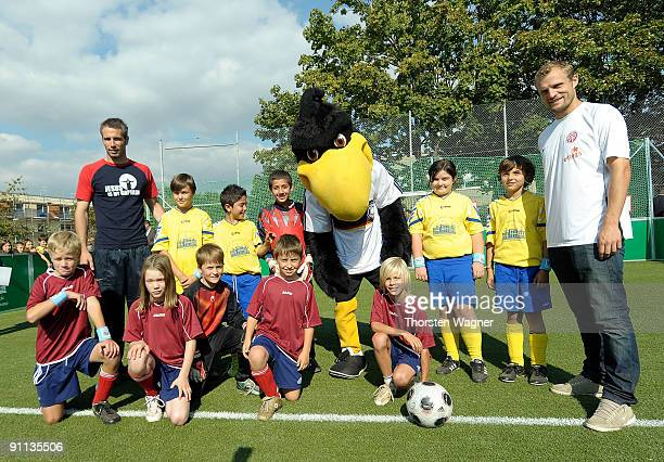 Player of Mainz 05 Marco Rose and Bo Svensson pose for a photo with children during the opening ceremony for the 1000 DFB Mini Soccer field at the...