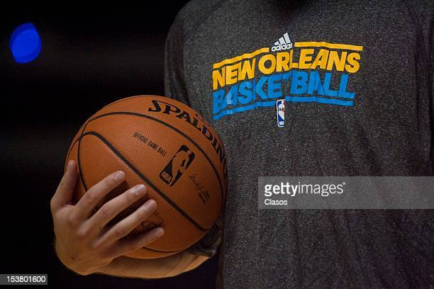 A player of New Orleans Hornets grabs a ball during a training session and Kids Day of New Orleans Hornets prior to a pre season game against Orlando...