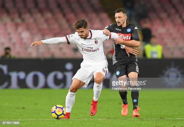 Player of SSC Napoli Mario Rui vies with AC Milan player Andre Silva during the Serie A match between SSC Napoli and AC Milan at Stadio San Paolo on...