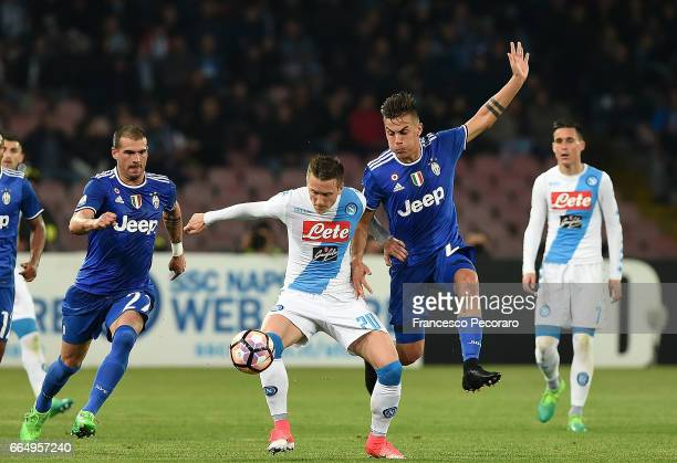 Player of SSC Napoli Piotr Zielinski vies with Juventus FC player Paulo Dybala during the TIM Cup match between SSC Napoli and Juventus FC at Stadio...