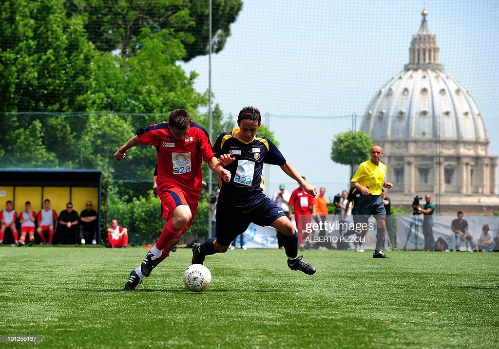 A player of the North American Martyrs (L) fights for the ball with a player of the Redemptoris Mater during the finale in the soccer final of the fourth Clericus Cup on May 29, 2010 at the Pontificio Oratorio San Pietro in Rome, near The Vatican. The Clericus Cup, is the football championship organized by the Vatican at the Italian sporting Center (CSI), a sport organization of the Catholic Church. AFP PHOTO / ALBERTO PIZZOLI