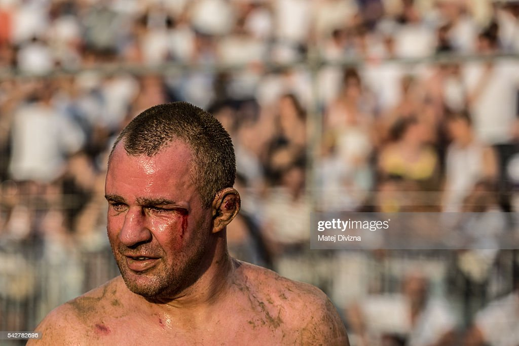 A player of the Santo Spirito Bianchi Team is seen during the final match of The Calcio Storico Fiorentino between the Santo Spirito Bianchi (White) Team and the La Santa Croce Azzuri (Blue) Team at the La Santa Croce square on June 24, 2016 in Florence, Italy. The Calcio Storico (Historical Football in English) Fiorentino is an early form of football, originating in the 1500's. It is a combination of football, rugby and wrestling. Now, annually during a weekend in early June, four teams representing the districts of Florence face each other in the first semi-finals. The winners go to the final, played every year on June 24, the day of the patron of Florence, St. John the Baptist. The official rules of calcio (football) were written for the first time in 1580 by Giovanni de Bardi, a count from Florence. The teams are formed by 27 players and the ball can be played either with hands or feet. Tactics such as punching, elbowing and all martial arts techniques are allowed but kicks to the are forbidden, as are fights of two or more against one. There is a referee, a field master, and six linesmen. The game lasts 50 minutes, and the winning team is the one who scores most points. The playing field is a giant sand pit with a narrow split constructing the goal running the width of each end. The Calcio Storico was not played for 200 years, until its revival in 1930.