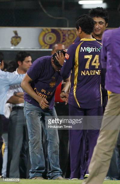 Player of the tournament Kolkata Knight Riders player Sunil Narine tries to hairdo for the team owner Shahrukh Khan after their victory against...