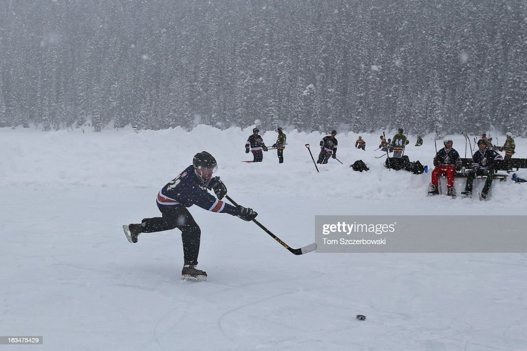 A player passes the puck during outdoor shinny hockey action at the 4th Annual Lake Louise Pond Hockey Classic on the frozen surface of Lake Louise on March 2, 2013 in Lake Louise, Alberta, Canada.