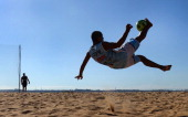 A player performs a bicycle kick as he trains with the Rio Branco Beach Soccer team in Vitoria Brazil on June 6 2014 Footballmad Brazil is preparing...