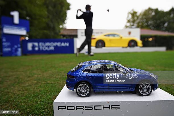 A player plays a shot infront of a Porsche car tee marker during the pro am prior to the start of the Porsche European Open at Golf Resort Bad...