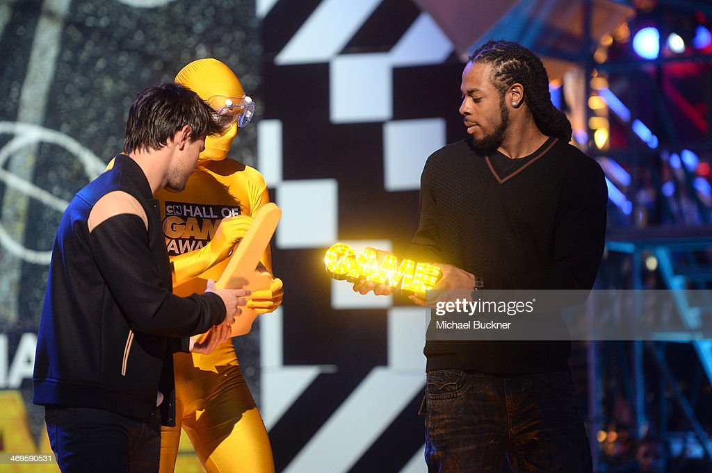 NFL player Richard Sherman (R) of the Seattle Seahawks accepts the Captain Clutch award from actor Taylor Lautner onstage during Cartoon Network's fourth annual Hall of Game Awards at Barker Hangar on February 15, 2014 in Santa Monica, California.