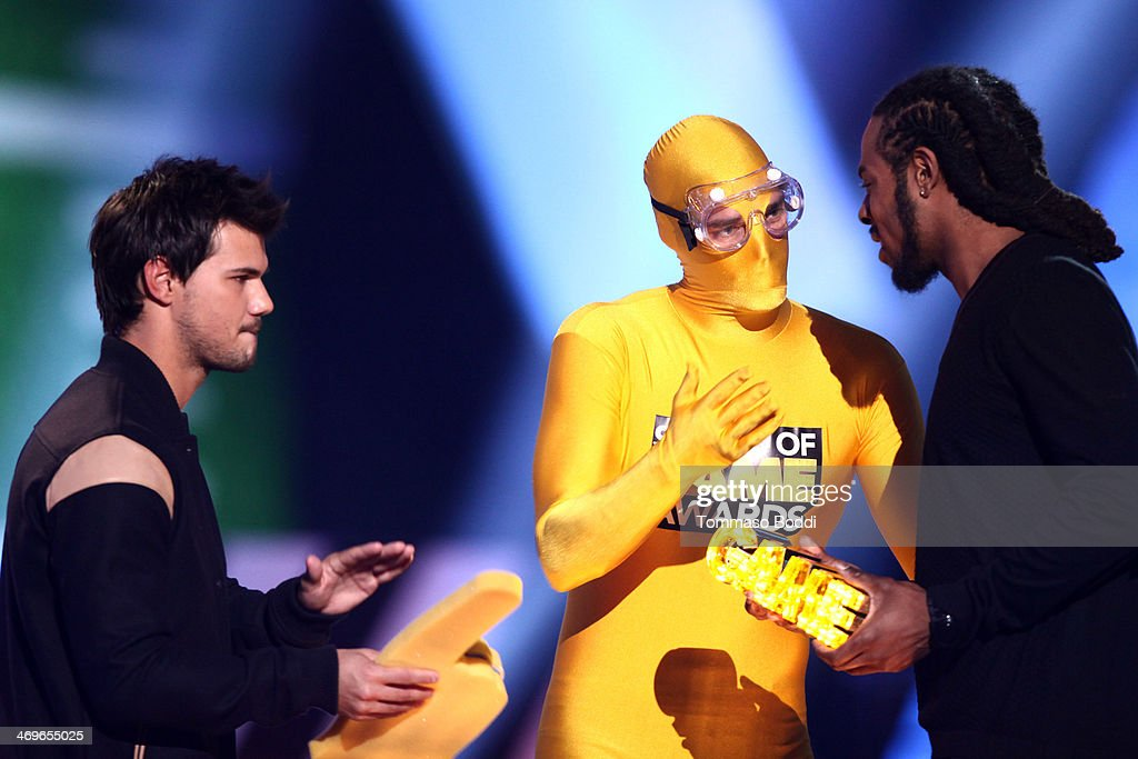 NFL player Richard Sherman (R) of the Seattle Seahawks accepts the Captain Clutch award from actor Taylor Lautner onstage during the 4th Annual Cartoon Network Hall Of Game Awards held at the Barker Hangar on February 15, 2014 in Santa Monica, California.