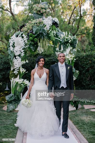 NBA player Russell Westbrook point guard for the Oklahoma City Thunder walks down the aisle with his bride Nina Earl during their outdoor wedding...
