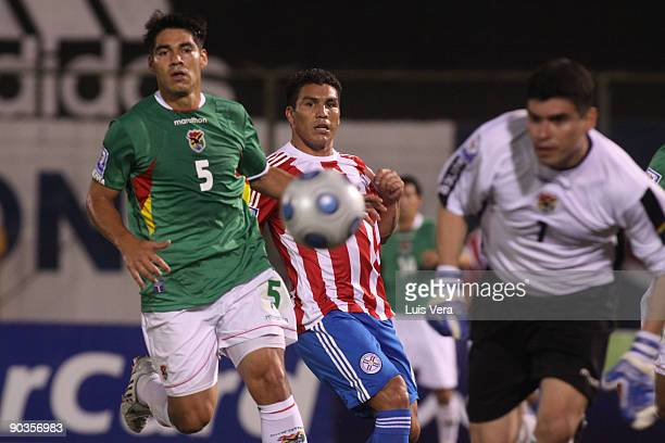 Player Salvador Cabanas of Paraguay vies for the ball with Luis Gutierrez and Hugo Suarez of Bolivia during the FIFAWorld Cup South Africa2010...