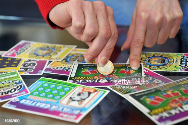 A player scratches a game card of the Française des Jeux the operator of France's national lottery on May 28 2013 in Nantes AFP PHOTO / FRANK PERRY