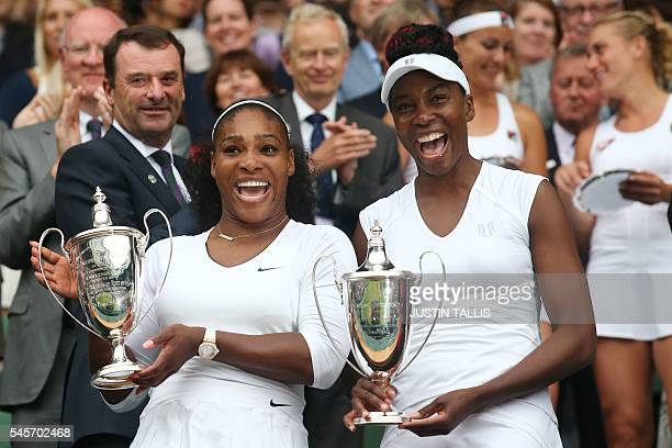 US player Serena Williams and her partner US player Venus Williams pose with the winner's trophies after beating Hungary's Timea Babos and...