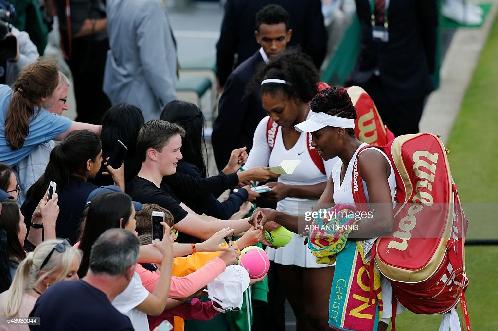 US player Serena Williams (2R) and her partner US player Venus Williams (R) sign autographs after beating Slovenia's Andreja Klepac and Katarina Srebotnik during their women's doubles first round match on the fourth day of the 2016 Wimbledon Championships at The All England Lawn Tennis Club in Wimbledon, southwest London, on June 30, 2016. / AFP / ADRIAN