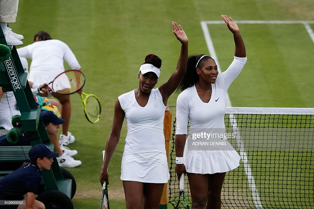 US player Serena Williams (R) and her partner US player Venus Williams (2R) wave to the crowd after beating Slovenia's Andreja Klepac and Katarina Srebotnik during their women's doubles first round match on the fourth day of the 2016 Wimbledon Championships at The All England Lawn Tennis Club in Wimbledon, southwest London, on June 30, 2016. / AFP / ADRIAN