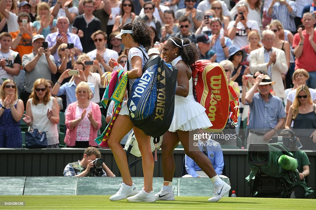 US player Serena Williams (R) and Switzerland's Amra Sadikovic (L) leave Centre Court together after Williams won their women's singles first round match on the second day of the 2016 Wimbledon Championships at The All England Lawn Tennis Club in Wimbledon, southwest London, on June 28, 2016. / AFP / GLYN