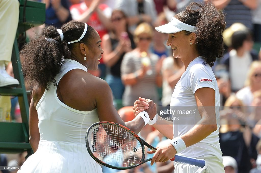 US player Serena Williams (L) and Switzerland's Amra Sadikovic (R) shake hands at the net after Williams won their women's singles first round match on the second day of the 2016 Wimbledon Championships at The All England Lawn Tennis Club in Wimbledon, southwest London, on June 28, 2016. / AFP / GLYN