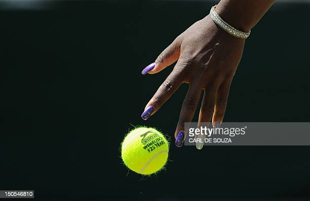 US player Serena Williams bounces the ball as she plays against Romania's Simona Halep in a Women's Singles match at the 2011 Wimbledon Tennis...