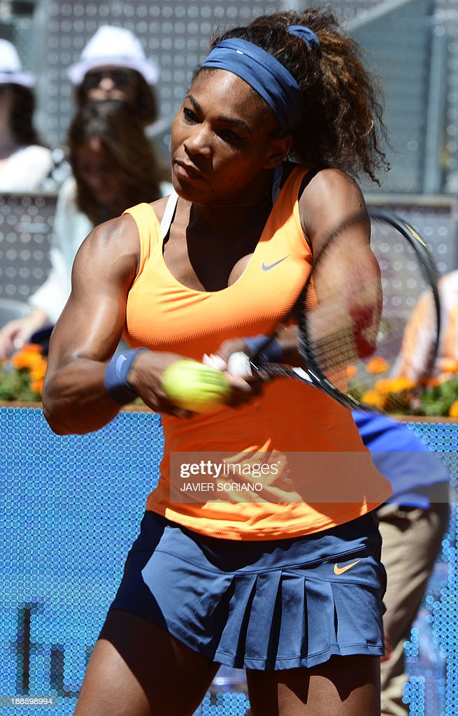 US player Serena Williams returns the ball to Russian player Maria Sharapova during their women's singles final tennis match at the Madrid Masters at the Magic Box (Caja Magica) sports complex in Madrid on May 12, 2013.