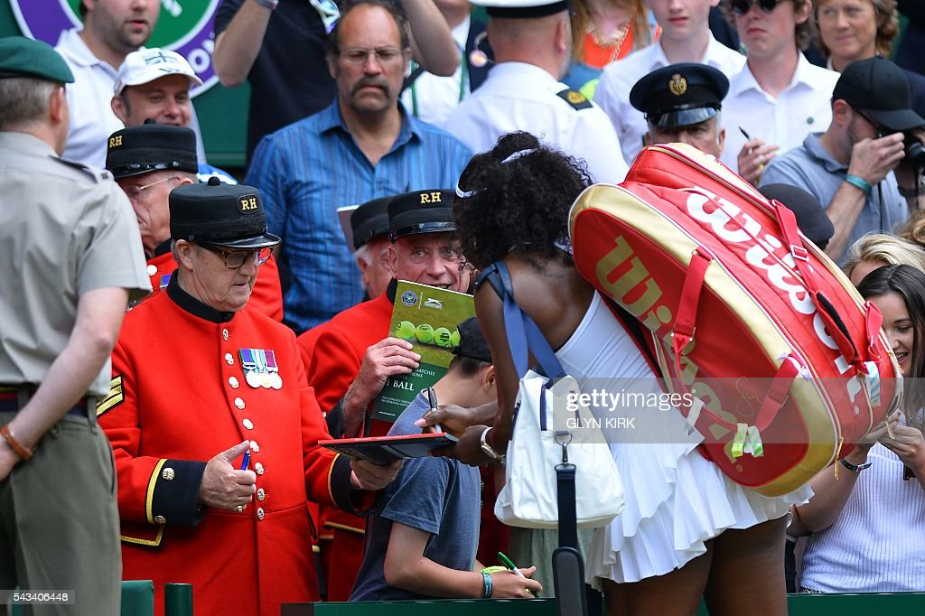US player Serena Williams (R) serves an autograph for a Chelsea Pensioner, a former British serviceman living at the Chelsea Royal Hospital, after beating Switzerland's Amra Sadikovic on Centre Court during their women's singles first round match on the second day of the 2016 Wimbledon Championships at The All England Lawn Tennis Club in Wimbledon, southwest London, on June 28, 2016. / AFP / GLYN