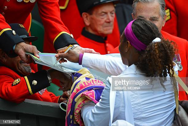 US player Serena Williams signs autographs for Chelsea Pensioners after her second round women's singles victory over Hungary's Melinda Czink on day...