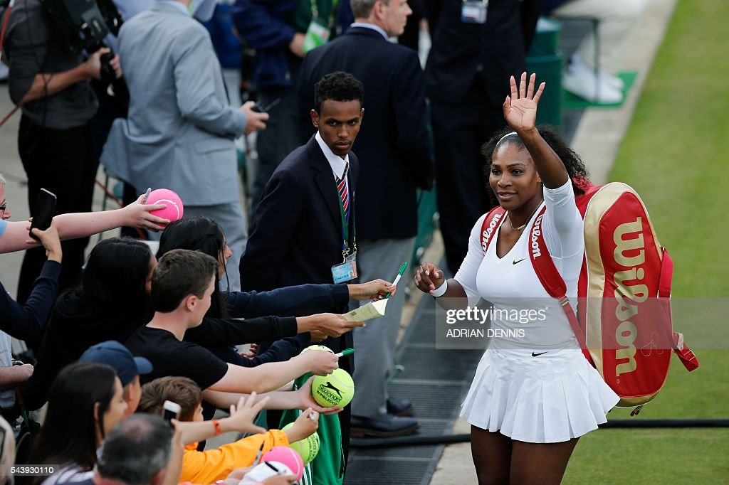 US player Serena Williams (R) waves after she and her partner US player Venus Williams (unseen) beat Slovenia's Andreja Klepac and Katarina Srebotnik during their women's doubles first round match on the fourth day of the 2016 Wimbledon Championships at The All England Lawn Tennis Club in Wimbledon, southwest London, on June 30, 2016. / AFP / ADRIAN