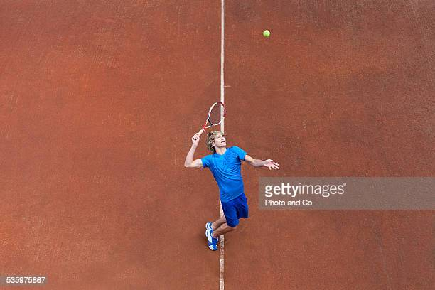 player serving the ball on clay court tennis