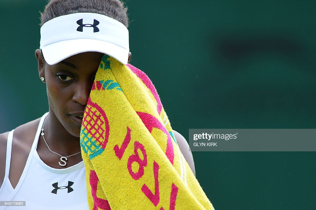 US player Sloane Stephens wipes her face while playing China's Peng Shuai during their women's singles second round match on the fourth day of the 2016 Wimbledon Championships at The All England Lawn Tennis Club in Wimbledon, southwest London, on June 30, 2016. / AFP / GLYN