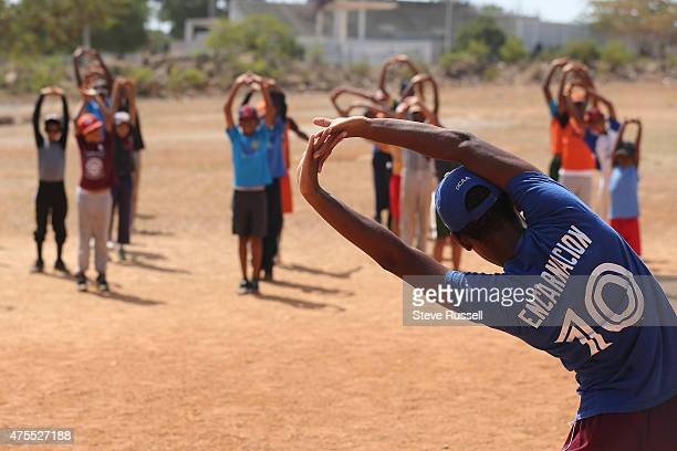 A player sporting an Edwin Encarnacion who is from the area shirt guides young players through stretches at the Academia de Beisbol Rafael Mejia S...