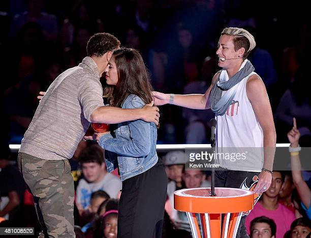 NBA player Stephen Curry accepts the Sickest Moves award from US Women's Soccer players Carli Lloyd and Abby Wambach onstage at the Nickelodeon Kids'...