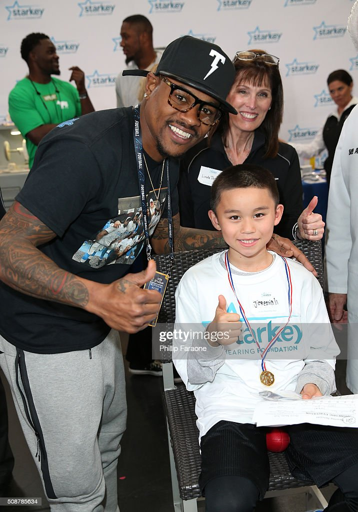 NFL player <a gi-track='captionPersonalityLinkClicked' href=/galleries/search?phrase=Ted+Ginn+Jr.&family=editorial&specificpeople=2106730 ng-click='$event.stopPropagation()'>Ted Ginn Jr.</a>, Linda Daily, Au.D. and patient Jeremiah give a thumbs up after Jeremiah was fitted with a hearing aid at the Starkey Hearing Foundation hearing mission during Super Bowl weekend 2016 at San Francisco State University on February 6, 2016 in San Francisco, California.