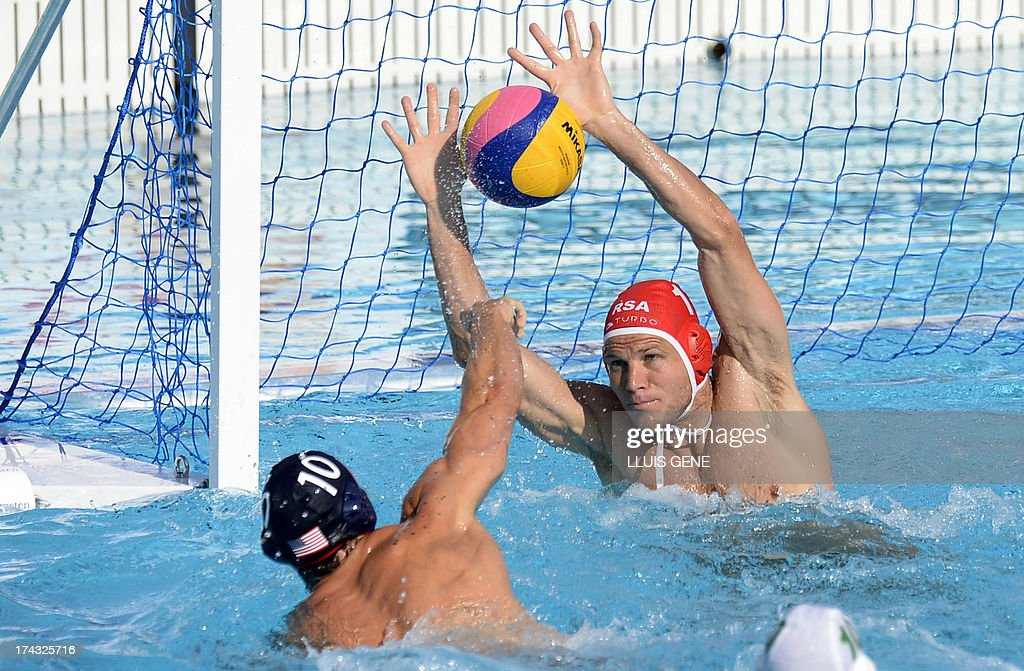 US player Timothy Hutten (L) shoots at South Africa's goalkeeper Dwayne Flatscher (R) during the preliminary round match of the men's water polo competition between the US and South Africa at the FINA World Championships at the Bernat Picornell swimming pool in Barcelona on July 24, 2013.