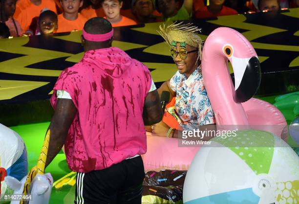 NFL player Von Miller and host Russell Wilson float in slime pool onstage during Nickelodeon Kids' Choice Sports Awards 2017 at Pauley Pavilion on...