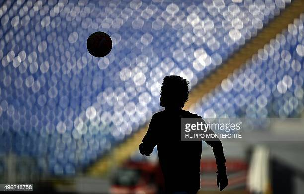 A player warms up in front of an empty 'Curva Sud' prior the Italian Serie A football match AS Roma vs SS Lazio at the Olympic Stadium in Rome on...
