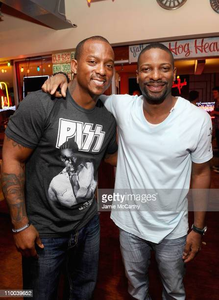 NFL player Willis McGahee of the Baltimore Ravens and DJ Irie attend the grand opening of Brother Jimmy's BBQ on March 12 2011 in St Maarten...