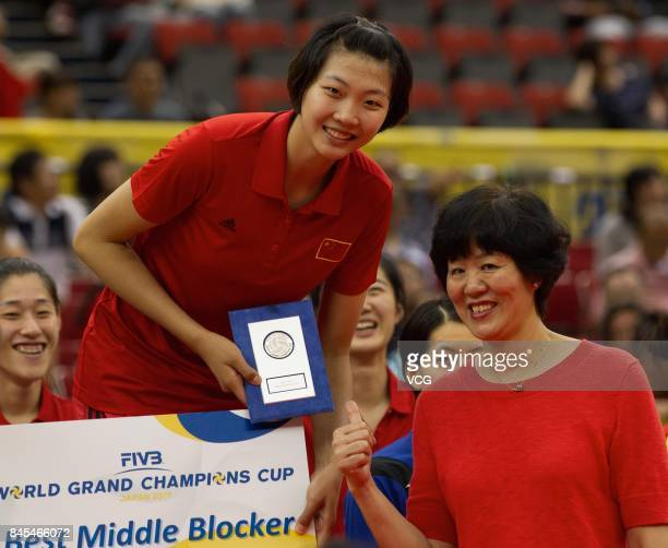 Player Yuan Xinyue and head coach Lang Ping of the Chinese national women's volleyball team pose with with Yuan Xinyue's trophy of the Best Middle...