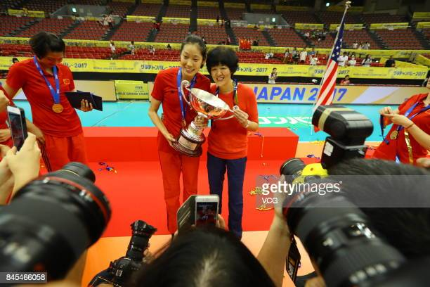 Player Zhu Ting and head coach Lang Ping of the Chinese national women's volleyball team pose with Zhu Ting's trophy of the Best Outside Spiker...