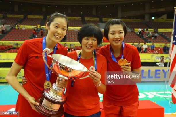 Player Zhu Ting head coach Lang Ping and player Yuan Xinyue of the Chinese national women's volleyball team pose with their trophy during the award...