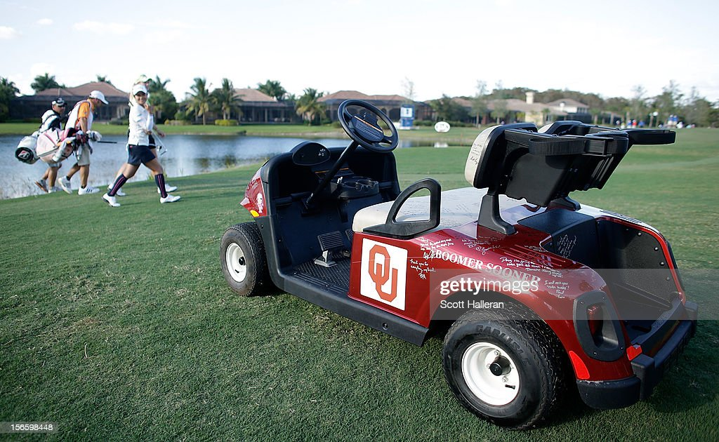 Players and caddies pass a golf cart on the 17th hole in memory of longtime rules official Doug Brecht who died after a three-month battle with the West Nile virus, during the third round of the CME Group Titleholders at the TwinEagles Club on November 17, 2012 in Naples, Florida.