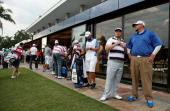 Players and caddies wait near the clubhouse after play was suspended by dangerous weather during the second round of the 2014 Brasil Champions...