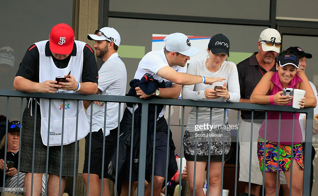 Players and caddies wait near the clubhouse after play was suspended by dangerous weather during the second round of the Volunteers of America Texas Shootout at Las Colinas Country Club on April 29, 2016 in Irving, Texas.