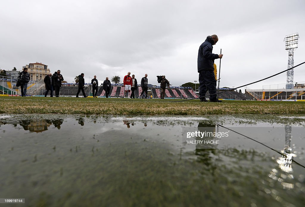 Players and coach walk on the ground as an employee of the stadium examines the field damaged by heavy rains some hours before the French Cup football match Nice vs Nancy, on January 23, 2013 at the Ray stadium in Nice. The local authority in charge of wheather forecast will decide if the match takes place.