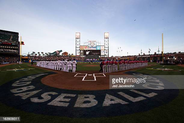 Players and coaches stand on the field during pregame ceremonies before the semifinal game between Team Puerto Rico and Team Japan in the...