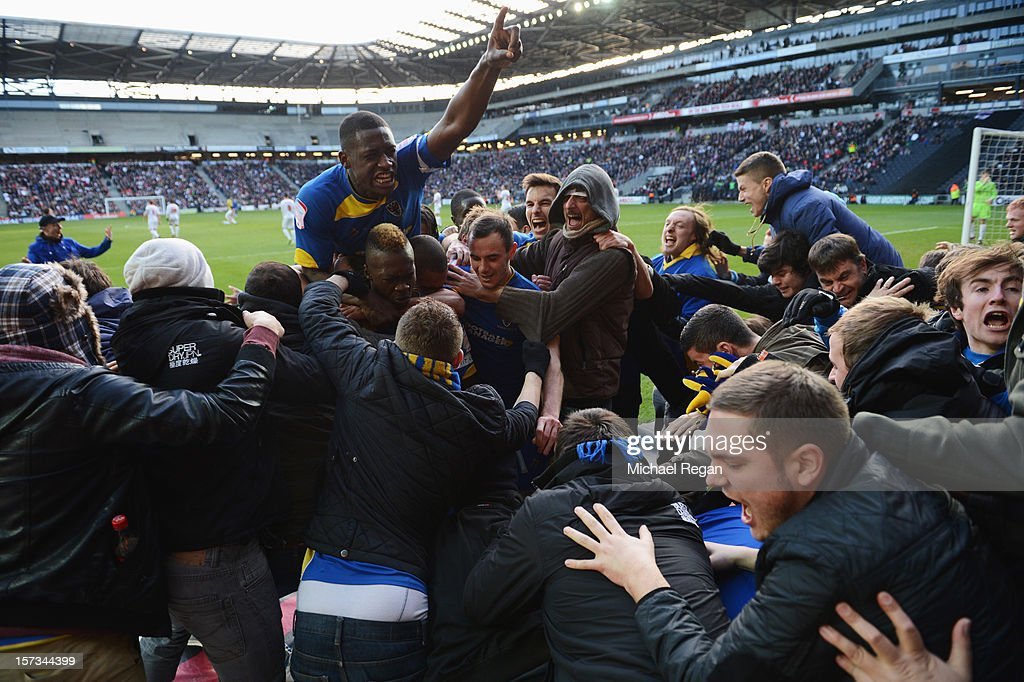 Players and fans celebrate as Jack Midson of AFC Wimbledon scores their first goal during the FA Cup with Budweiser Second Round match between MK Dons and AFC Wimbledon at StadiumMK on December 2, 2012 in Milton Keynes, England. This match is the first meeting between the two teams following the formation of AFC Wimbledon (the football club formed in 2002 by supporters unhappy with their club's relocation to Milton Keynes) and the MK Dons (which Wimbledon F.C. controversially became).