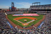 Players and fans observe the national anthem as the stars and stripes is presented by members of the US military as the Colorado Rockies host the San...