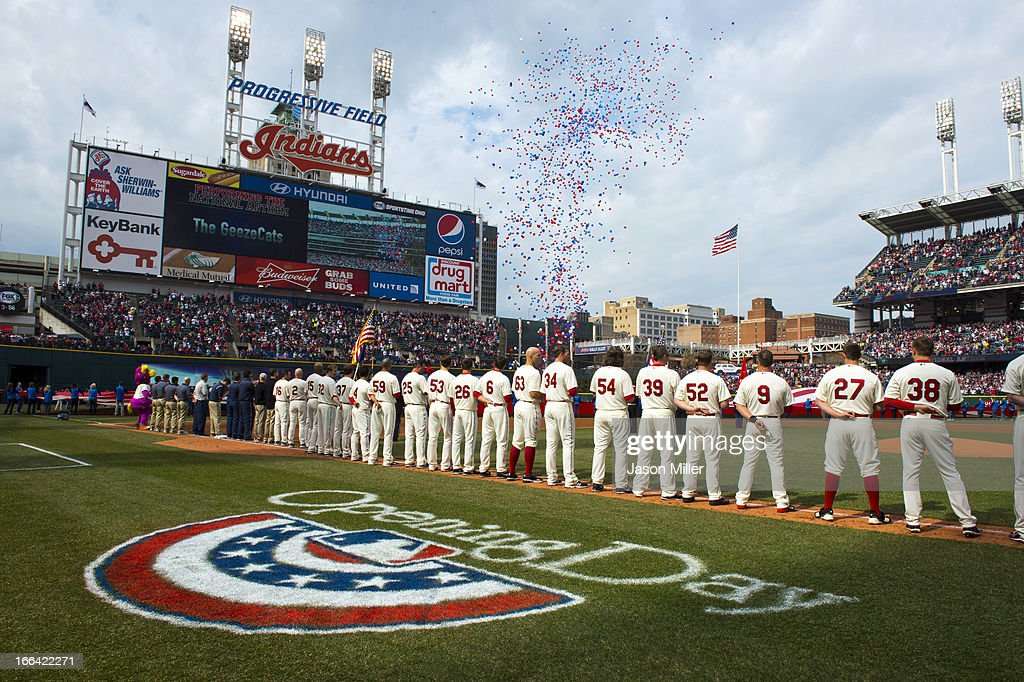 Players and fans salute the flag during the national anthem prior to the game between the Cleveland Indians and the New York Yankees on opening day at Progressive Field on April 8, 2013 in Cleveland, Ohio.